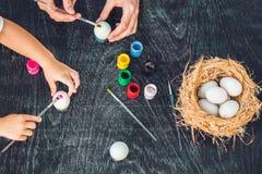 Madre felice di pasqua A, padre ed il loro figlio dipingenti le uova di Pasqua Famiglia felice che prepara per Pasqua Immagine Stock Libera da Diritti
