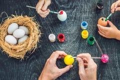 Madre felice di pasqua A, padre ed il loro figlio dipingenti le uova di Pasqua Famiglia felice che prepara per Pasqua Fotografie Stock