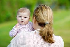 Madre felice divertendosi con la figlia del neonato all'aperto fotografia stock libera da diritti