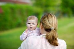 Madre felice divertendosi con la figlia del neonato all'aperto immagini stock