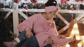 Madre felice divertendosi con sua figlia del bambino vicino all'albero di Natale maternità stock footage