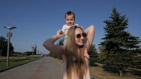 Madre felice e bambino all'aperto che camminano nel giorno di estate stock footage