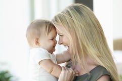 Madre felice e bambino che sorridono negli occhi di ciascuno Immagini Stock Libere da Diritti