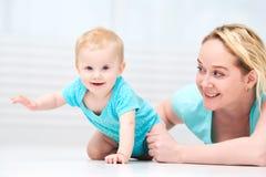 Madre felice e bambino infantile crowling fotografia stock libera da diritti