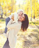 Madre felice e bambino sorridenti che giocano divertendosi in autunno Fotografie Stock Libere da Diritti