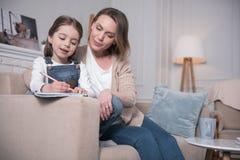 Madre felice e figlia che si siedono sul sofà Fotografia Stock