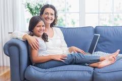 Madre felice e figlia che si siedono sullo strato e che per mezzo del computer portatile Fotografia Stock