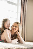 Madre felice e figlia che si trovano sul pavimento a casa Fotografia Stock Libera da Diritti