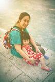 Madre felice e figlia che sorridono e che si rilassano all'aperto, viaggio Fotografia Stock