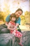 Madre felice e figlia che sorridono e che si rilassano all'aperto, viaggio Immagine Stock Libera da Diritti