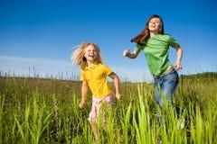 Madre felice e figlia fatte funzionare sul campo Fotografia Stock