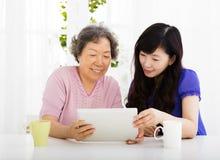 Madre felice e figlia senior che imparano il pc della compressa fotografie stock
