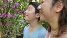 Madre felice e figlio asiatici della famiglia che camminano nel giardino dell'orchidea con il fronte di sorriso video d archivio