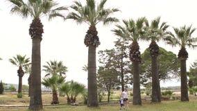 Madre felice e figlio che camminano nel parco fra le palme in Turchia stock footage