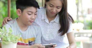 Madre felice e figlio della famiglia che giocano insieme gioco sul telefono cellulare mobile stock footage