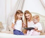 Madre felice e le sue piccole figlie divertendosi facendo uso di una compressa Fotografie Stock Libere da Diritti