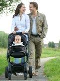 Madre felice e padre che sorridono e che spingono la carrozzina del bambino con il bambino Fotografia Stock