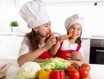 Madre felice e piccola figlia in cappello del cuoco e del grembiule che mangiano le carote che si divertono insieme a casa cucina Fotografia Stock Libera da Diritti