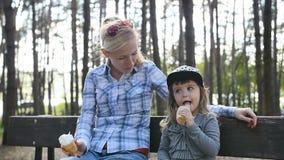 Madre felice e piccola figlia che mangiano il gelato sul banco stock footage