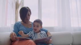 Madre felice e piccolo figlio che leggono un libro di mattina insieme nel salone a casa concetto di attivit? della famiglia stock footage