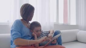 Madre felice e piccolo figlio che leggono un libro di mattina insieme nel salone a casa concetto di attivit? della famiglia video d archivio