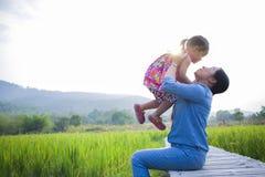 Madre felice e suo il gioco da bambini all'aperto che si divertono, terra posteriore del giacimento verde del riso immagine stock