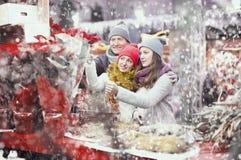 Madre felice, padre e ragazza teenager compranti euforbia e flo rossi Immagini Stock Libere da Diritti