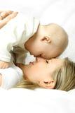 Madre felice sul sofà con il suo bambino immagine stock