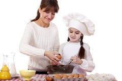 Madre feliz con cocinar alegre de la pequeña hija Fotos de archivo libres de regalías