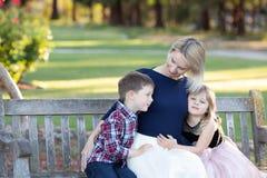 Madre feliz con dos niños que se sientan en un banco de madera en un jardín imagen de archivo libre de regalías