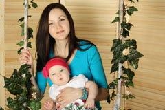 Madre feliz con el bebé sonriente en el oscilación Imagen de archivo libre de regalías