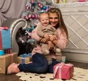 Madre feliz con el hijo recién nacido, sentándose en un piso cerca de un árbol de navidad Esperar un día de fiesta Imágenes de archivo libres de regalías