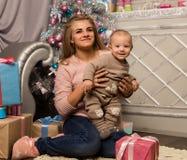 Madre feliz con el hijo recién nacido, sentándose en un piso cerca de un árbol de navidad Esperar un día de fiesta Fotografía de archivo libre de regalías