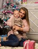 Madre feliz con el hijo recién nacido, sentándose en un piso cerca de un árbol de navidad Esperar un día de fiesta Imagenes de archivo