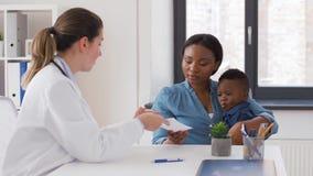 Madre feliz con el hijo y el doctor del bebé en la clínica almacen de video