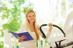 Madre feliz con el libro y el cochecito en parque Imágenes de archivo libres de regalías