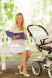 Madre feliz con el libro y el cochecito en parque Fotos de archivo
