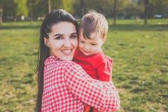 Madre feliz con el niño en el parque Foto de archivo