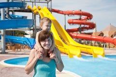 Madre feliz con el niño en el aquapark Foto de archivo libre de regalías