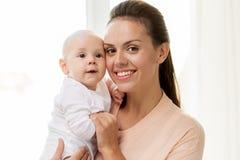 Madre feliz con el pequeño bebé en casa imagenes de archivo