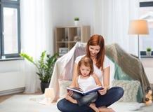 Madre feliz con el pequeño libro de lectura de la hija Fotos de archivo libres de regalías