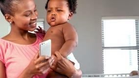 Madre feliz con el teléfono que levanta a su bebé almacen de metraje de vídeo