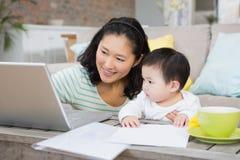 Madre feliz con la hija del bebé que usa el ordenador portátil Foto de archivo libre de regalías