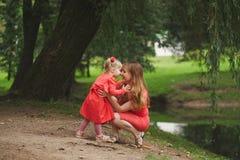Madre feliz con la hija en vestidos rojos Foto de archivo