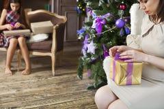 Madre feliz con la hija que envuelve los regalos de la Navidad en casa cerca Imagenes de archivo