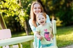 Madre feliz con la hija que se sienta en el children& x27; silla de s Foto de archivo