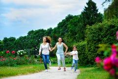 Madre feliz con la hija y el hijo que corren encendido imagen de archivo