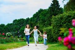 Madre feliz con la hija y el hijo que corren encendido imágenes de archivo libres de regalías