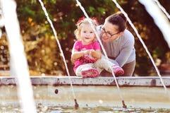 Madre con la niña cerca del fontain Fotos de archivo libres de regalías