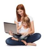 Madre feliz con la niña y el ordenador portátil adorables Imágenes de archivo libres de regalías